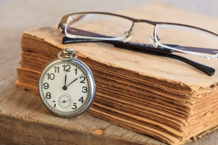 Pocket watch next to ancient softcover book with glasses on top photo
