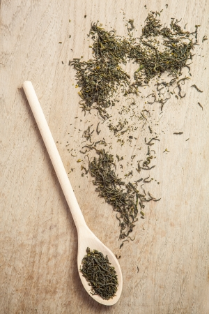 Loose dried green tea  on a wooden spoon and table. photo