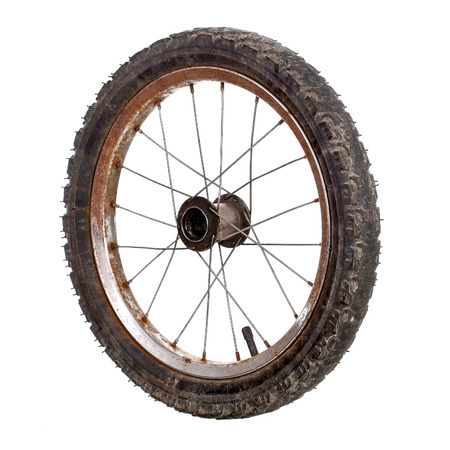 Small rusty old bicycle wheel isolated on white photo