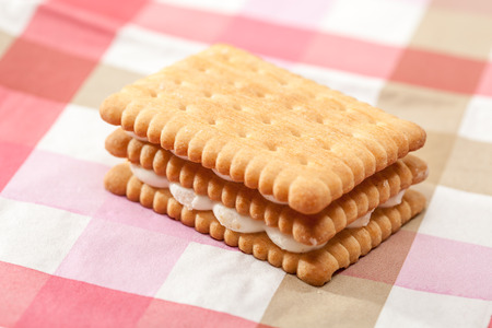 Sandwich cookie with white cream on a pink tablecloth photo