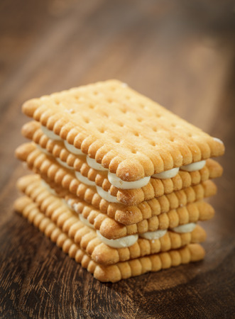 Sandwich cookies on brown wooden table. Shallow depth of field photo