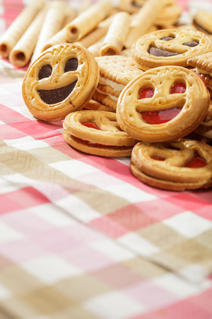 Pile of cookies and tubules on pink tablecloth photo