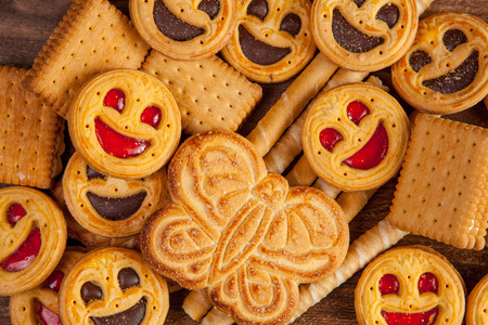 tubules: Round cookies with smiling faces, sweet tubules, butterfly and sandwich cookies background