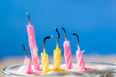 Six extinct birthday candles over blue background photo