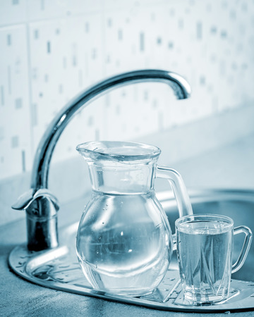 Glass jug and cup with water by the kitchen tap photo