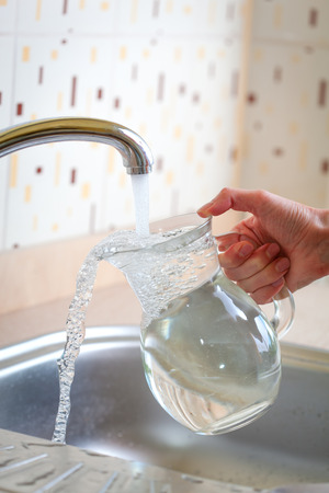 Hand holding jug under water tap photo