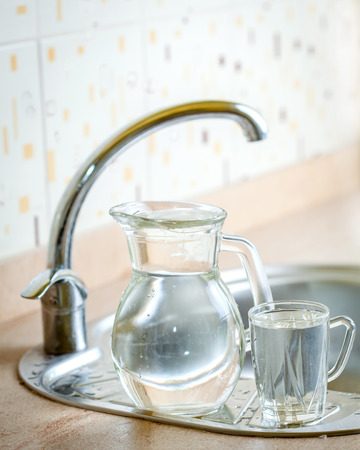 Full jug next to full glass on sink photo