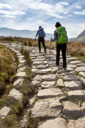 park path: SNOWDONIA PARK, WALES, UK - September 18, 2014: Two hikers with sticks on Llanberis path to Snowdon mountain. Llanberis Path is the longest and most gradual of the six main paths to the summit of Snowdon mountain Editorial