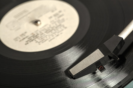 Old vinyl record spinning on turntable photo