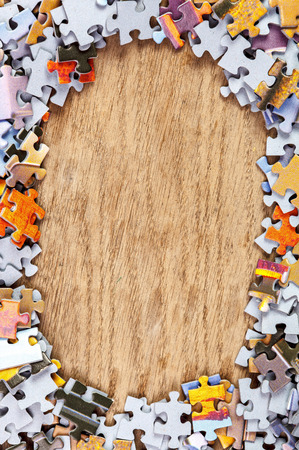 Frame of jigsaw puzzle pieces on wooden background