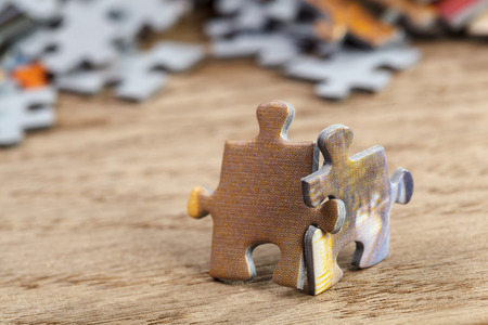 Two jigsaw puzzle pieces on a table joint together