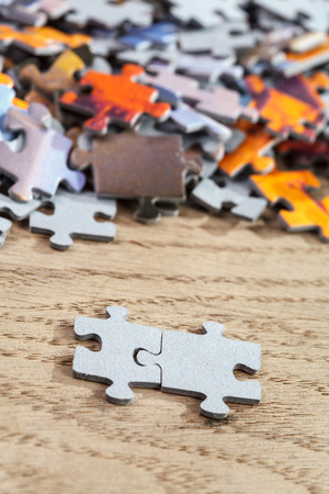 puzzle jigsaw: Closeup of two connected jigsaw puzzle pieces on a table Stock Photo