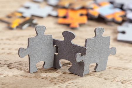 Three jigsaw puzzle pieces on a table joint together Stockfoto