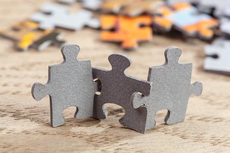 piezas de rompecabezas: Tres rompecabezas de piezas en una articulación mesa juntos Foto de archivo