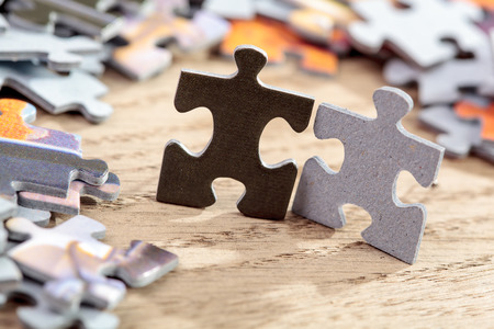 business symbols metaphors: closeup of black and grey jigsaw puzzle pieces on table