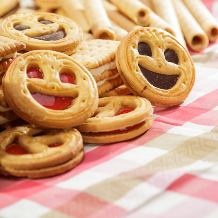 Pile of cookies with smiling faces and tubules on pink tablecloth photo