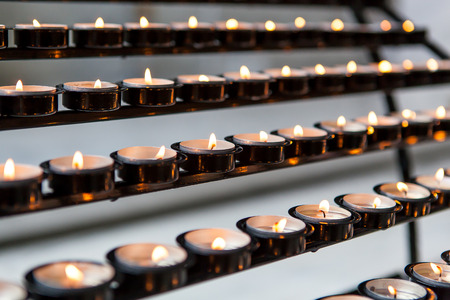 votive: Rows of burning votive candles. Shallow depth of field