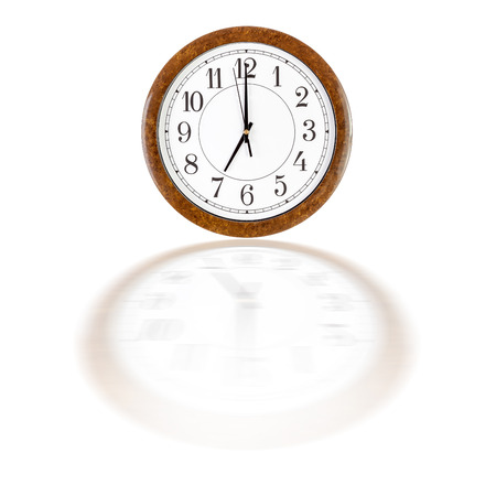 seven o'clock: A white clock face in brown wooden frame showing seven oclock over white background with blurry reflection Stock Photo