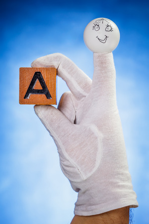 glove puppet: Finger puppet holding wooden cube with capital letter A over blue background