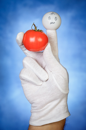glove puppet: White finger puppet holding tomato fruit with confused face expression Stock Photo