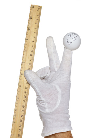 glove puppet: Finger puppet holding wooden rule over white background Stock Photo