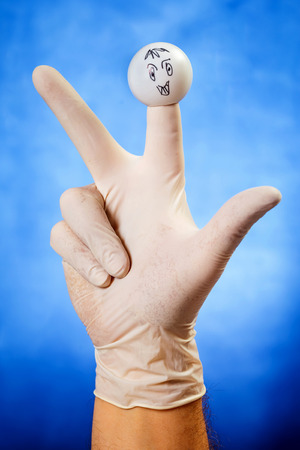 glove puppet: Hand in white latex glove with angry finger puppet over blue background