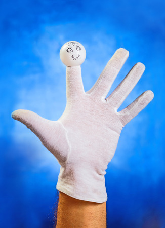 glove puppet: Opened palm in white glove with angry finger puppet over blue background
