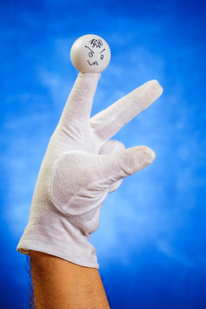 glove puppet: Hand in white glove with angry finger puppet over white background Stock Photo