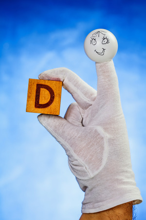 glove puppet: Finger puppet holding wooden cube with capital letter D over blue background