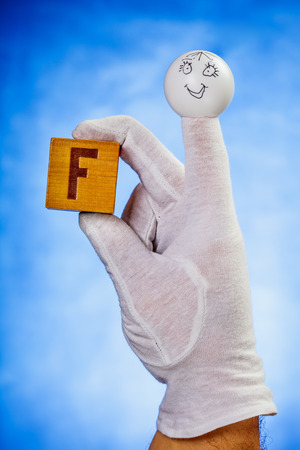 glove puppet: Finger puppet holding wooden cube with capital letter F over blue background