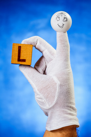 glove puppet: Finger puppet holding wooden cube with capital letter L over blue background
