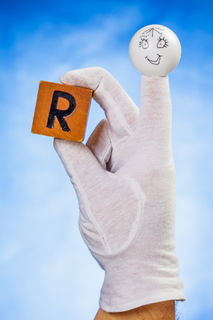 glove puppet: Finger puppet holding wooden cube with capital letter R over blue background