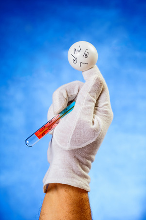 Concept of illness: finger puppet with medical thermometer showing forty point four degrees celsius photo