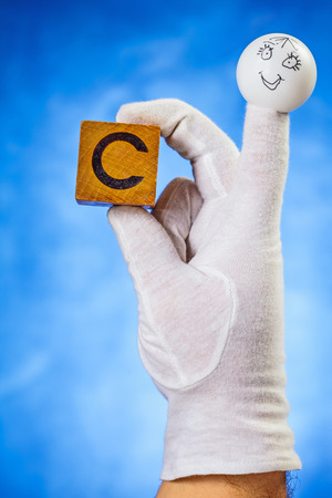 glove puppet: Finger puppet holding wooden cube with capital letter C over blue background