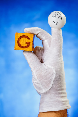 glove puppet: Finger puppet holding wooden cube with capital letter G over blue background