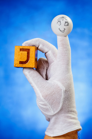 glove puppet: Finger puppet holding wooden cube with capital letter J over blue background Stock Photo
