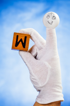 glove puppet: Finger puppet holding wooden cube with capital letter W over blue background