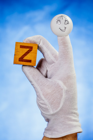 glove puppet: Finger puppet holding wooden cube with capital letter Z over blue background