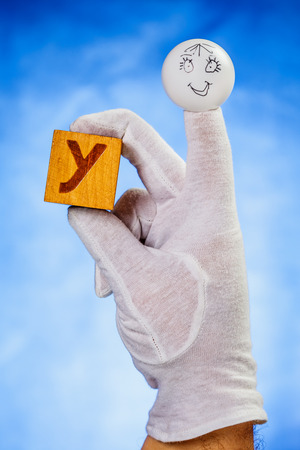 glove puppet: Finger puppet holding wooden cube with capital letter Y over blue background