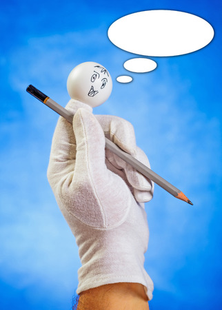 glove puppet: Happy finger puppet holding sharp pencil with speech bubble against blue background
