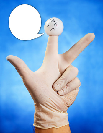 glove puppet: Hand in white glove with angry finger puppet with speech bubble against blue background Stock Photo