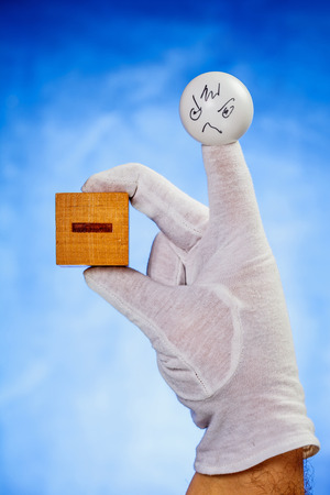 glove puppet: Finger puppet with angry face expression holds wooden cube with minus sign over blue background