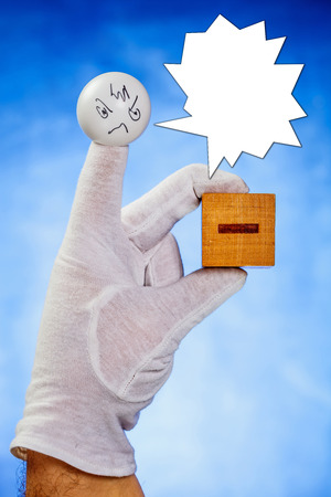 Finger puppet with angry face expression and talking bubble holds wooden cube with minus sign over blue background photo