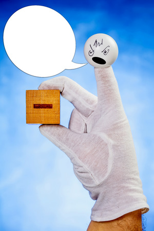 glove puppet: Angry finger puppet speaking into speech bubble holds wooden cube with minus sign over blue background