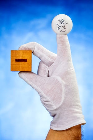 glove puppet: Finger puppet with confused face expression holds wooden cube with minus sign over blue background