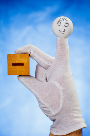 glove puppet: Finger puppet with smiling face face holds wooden cube with minus sign over blue background