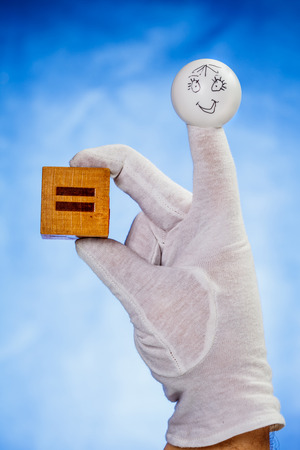glove puppet: Finger puppet with smiling face holds over blue background wooden cube with equal sign Stock Photo