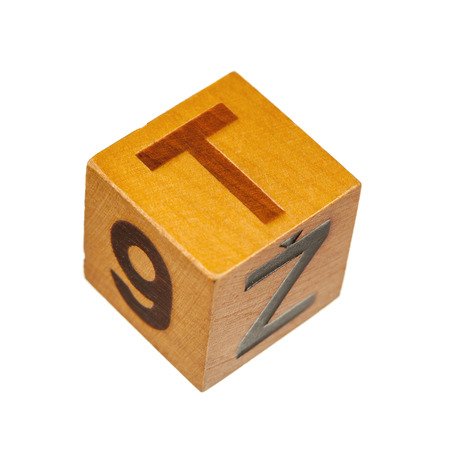 t square: Wooden block with capital T letter isolated over white background. Shallow depth of field