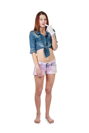 short gloves: Young attractive girl in purple shorts and jeans shirt holding by mouth finger in white glove over white background