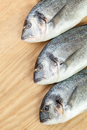 daurade: Three dorado fishes on wood board Stock Photo